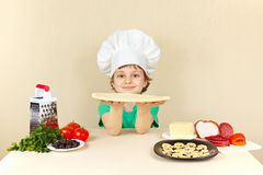 Young smiling chef at the table with ingredients is going to cook pizza Stock Images