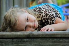 Young smiling child lying down at the playground Royalty Free Stock Image
