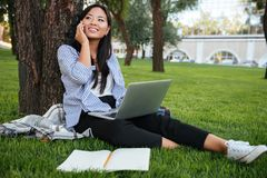 Young smiling chinese student speaking mobile phone, holding com. Puter, sitting on grass, outdoor Stock Images