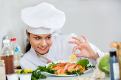Young  smiling cook arranging shrimps Stock Image