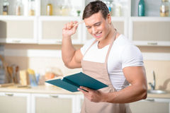 Young smiling cook is reading a cookbook Stock Photo