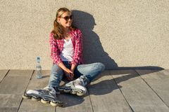Young smiling cool girl shod in rollerblades, sits on the sidewa Royalty Free Stock Photography