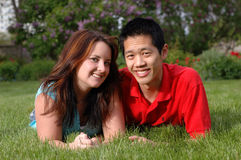 Young smiling couple. Young people recline on the lawn Stock Photography