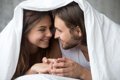 Young smiling couple in bed having fun covered with blanket. Young smiling couple in bed having fun covered with soft warm blanket duvet, happy playful stock photos
