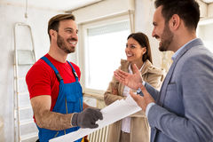 Young smiling couple and builder handyman talking about details. Young smiling couple and handyman talking about details of renovations home stock photo
