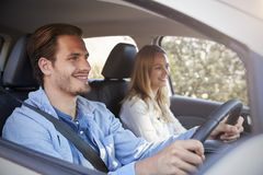 Young smiling couple in a car on a road trip looking ahead Royalty Free Stock Images