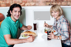 Young smiling couple enjoying lunch Royalty Free Stock Photography