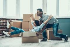 Young Smiling Couple Having Fun Unpacking Boxes royalty free stock photos