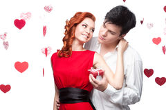 Young smiling couple holding small red gift Royalty Free Stock Photos