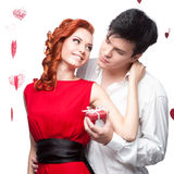 Young smiling couple holding small red gift Stock Photos