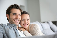 Young smiling couple looking towards future. Couple at home relaxing in sofa Royalty Free Stock Photography