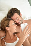 Young smiling couple lying in bed using smartphone. Couple laying in bed using smartphone Royalty Free Stock Photos