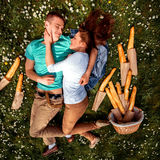 Young smiling couple lying and dreaming on the grass with basket Stock Photography
