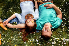 Young smiling couple lying and dreaming on the grass with flower Stock Image