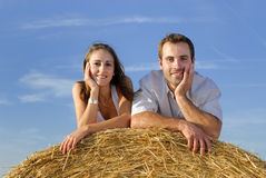 Young smiling couple lying on a straw bale Royalty Free Stock Photography