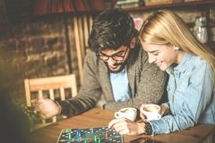 Day with friend. Playing leisure game. Young smiling couple playing leisure games together at cafe.Close up Royalty Free Stock Images