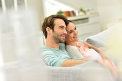 Young smiling couple relaxing on sofa Stock Photos