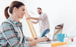 Happy couple remodeling their house. Young smiling couple renovating and remodeling their new apartment, the men is painting the walls with a roller and the Stock Photos