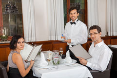 Young smiling couple at the restaurant Stock Image