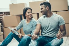 Young Smiling Couple Resting after Packing Boxes. Two Young People in Love look at each other after Packing Carton Boxes. Happy Couple Prepearing to Move out royalty free stock image