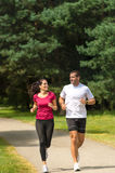Young smiling couple running in park. Smiling young couple running in park Stock Photo