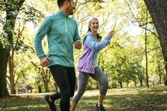 Young smiling couple running at park. Exercise in nature. On the move Royalty Free Stock Image