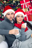 Young and smiling couple with santa hat relaxing in X- mas night. Young couple in Christmas night drinking hot tea in the background Christmas tree with presents royalty free stock photos