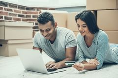 Young Smiling Couple Shopping Online on Laptop royalty free stock photos