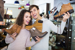 Young smiling couple shopping at shoe store Royalty Free Stock Image