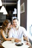 Young smiling couple sitting at cafe with cups of coffe, cake and hugging. royalty free stock photos