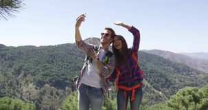 Young smiling couple taking picture of themselves. Young smiling couple hiking in mountains in summer time and making self portrait stock video footage