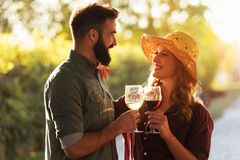 Young smiling couple tasting wine at winery vineyard stock photos