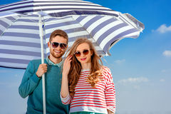 Young smiling couple under the umbrella on blue sky background Stock Photos