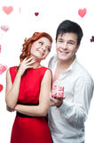 Young smiling couple on valentines day. Young smiling man and woman in red dress holding small red gift stock photos