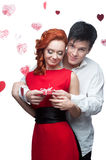 Young smiling couple on valentines day. Young smiling man and woman in red dress holding small red gift stock photo