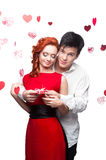 Young smiling couple on valentines day. Young smiling man and woman in red dress holding small red gift stock photography