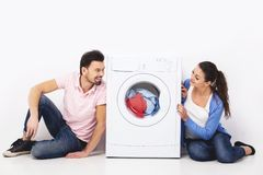 Young smiling couple with a washing machine, on the white background στοκ εικόνα