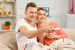 Young smiling couple watching TV on the sofa Stock Image
