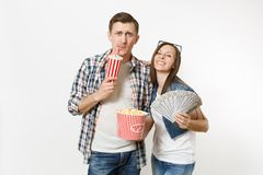 Young smiling couple, woman and man watching movie film on date holding bucket of popcorn plastic cup of soda or cola. Young smiling couple, women and men royalty free stock photos