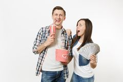 Young smiling couple, woman and man watching movie film on date holding bucket of popcorn plastic cup of soda or cola. Young smiling couple, women and men royalty free stock photo