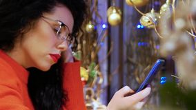 Girl in glasses holding smartphone. Young smiling curly woman in glasses, a red sweater and with red lips with a phone on a background of Christmas decor. Girl stock footage
