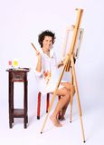 Young smiling curly woman painter Royalty Free Stock Photography