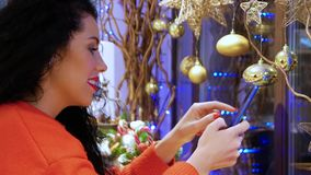 Girl holding a smartphone. Young smiling curly woman in a red sweater and with red lips with a phone on the background of Christmas decor. Girl holding a stock video footage