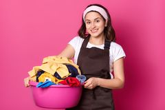 Young smiling cute female walking with pink basin, having much laundry, holding it with both hands, looks positive and sincere. royalty free stock photography