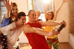 Dancers group taking selfie in dancing studio. Young smiling dancers group taking selfie in dancing studio Stock Images