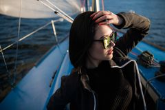 Young smiling dark-haired woman wearing sunglasses sitting on a board of boat in sunny autumn day, walking on a sea or royalty free stock photos
