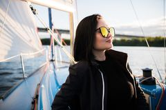 Young smiling dark-haired woman wearing sunglasses sitting on a board of boat in sunny autumn day, walking on a sea or royalty free stock photo