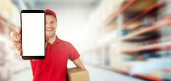 Young smiling delivery service courier showing blank smart phone at warehouse royalty free stock image