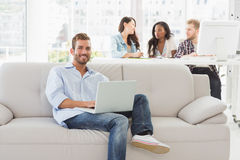 Young smiling designer working on his laptop on the couch Royalty Free Stock Photos