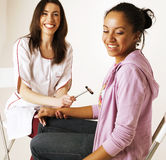 Young smiling doctor examine patient, measuring pressure to smiling afro american woman, happy lifestyle people Royalty Free Stock Photos